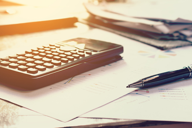 Calculator and pen, signifying preparation of taxes